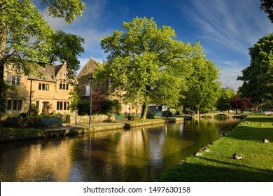 Cafe and Village Hall in morning sun reflected in River Windrush with sleeping ducks and bridge in Bourton-on-the-Water village in the Cotswolds Bourton-on-the-Water, England - June 13, 2019