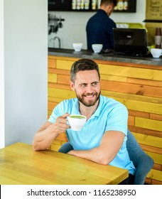 Cafe visitor happy smiling face enjoy coffee drink. Improve overall health. Take moment to care about yourself. Coffee drinkers live longer. Man bearded guy drinks cappuccino wooden table cafe.