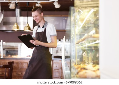 Cafe waiter or young small business owner staff serving cafeteria apron concept. Bakery manager making notes or accepts an order