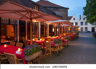 Cafes and restaurants with cozy terraces at nighttime in Bruges, Belgium