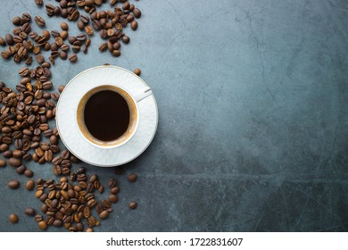 Cafes and restaurants. A mug of invigorating, black coffee and coffee beans on dark gray background. Place for an inscription. The concept of hot drinks.