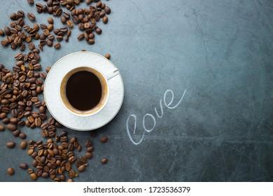 Cafés und Restaurants. Ein Schlamm belebender, schwarzer Kaffee und Kaffeebohnen auf dunkelgrauem Hintergrund. Ort für eine Inschrift. Das Konzept der heißen Getränke.