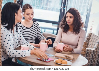 In the cafeteria. Beautiful nice women sitting together around the table while having tea