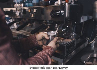 Caffe Bar Barista heating milk in a barista jug pitcher preparing fresh coffe