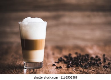 Caffe latte layered with milk in a high drinking glass. There are roasted coffee beans spread out on the wooden table next to the glass, and the background is also wooden.
