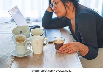 Caffeine addicted bad lifestyle concept. Young Asian woman holding a cup of coffee sitting tired with many empty cups of coffee and laptop on the desk. Focus on the hand and coffee.
