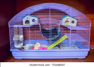 Cage for small Pets - rats, mice, rabbits, etc. . In the cage you can see two toy house, a drinking bottle and other different things
