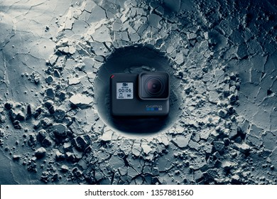 Cagliari, Italy 01/04/2019; GoPro camera that impacted on a surface creating a crater. Illustrative product photo of GoPro camera which emphasizes compactness solidity and resistance.
