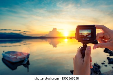 Cagliari, Italy 28-08-2019; GoPro Hero 7 Black action camera on female hands taking pictures of the sunset on the calm pond.