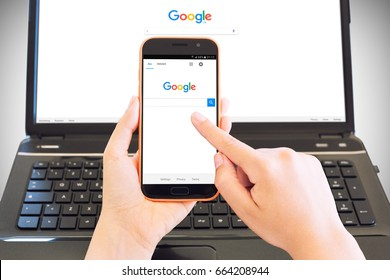 Cagliari, Italy - 30/05/2017: Smartphone on female hands browsing Google Home Page and in background a portable computer with the same site - this is an illustrative editorial image.