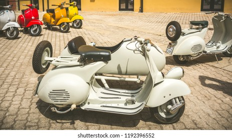 Cagliari, Italy - April 29, 2018: Piaggio Vespa vintage scooters meeting. Vintage Vespa with Sidecar from the 50s. Post process in vintage style.