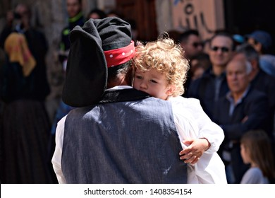 Cagliari / Italy - May 1 2019: 363° edition of Sant'Efisio religious/folk procession. A father carries his blod son in his arms at the parade