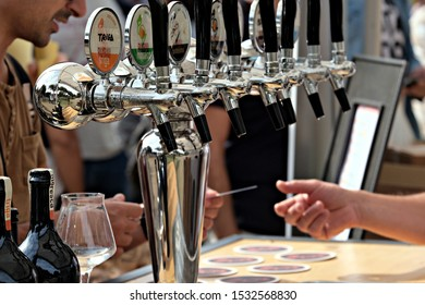 """Cagliari / Italy - October 12 2019: """"Orti Arti e Giardini"""" a public event dedicated to gardening and food. Close up of a row of taps for draft beers, on background hands with a credit card"""