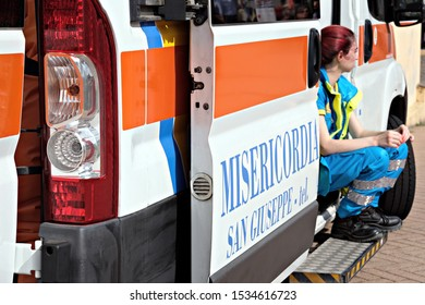 """Cagliari / Italy - October 12 2019: """"Orti Arti e Giardini"""" a public event dedicated to gardening and food. An Emergency Medical Technician on the ambulance during a break. Focus on the light"""