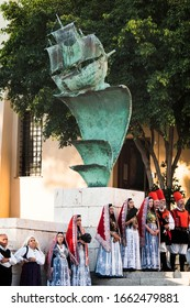 CAGLIARI, SARDINIA, ITALY - SEPTEMBER 29th 2019 : Bronze sailboat sculpture at the Sanctuary of the Bonaria before a big green tree. Men and women in the sardinian traditional costume before the sails