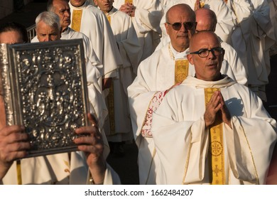 CAGLIARI, SARDINIA, ITALY - SEPTEMBER 29th 2019 : Religious procession of white and gold dressed priests during the ceremony of the Blessd Mary of the Bonaria jubilee, carrying a holy silvered book .