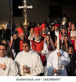 CAGLIARI, SARDINIA, ITALY - SEPTEMBER 29th 2019 : Procession of Sardinian people in traditional costumes. A priest is carrying a big and hight crucifix and another has a candlestick with a big candle.