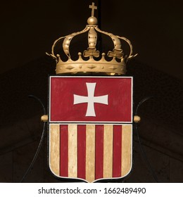 CAGLIARI, SARDINIA, ITALY - SEPTEMBER 29th 2019 : Blazon with a white cross on a red background upside and red and golden vertical lines down, topped by a golden crown with a cross