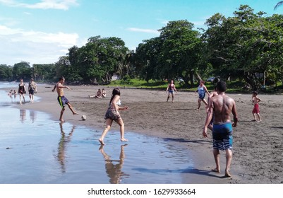 Cahuita, Costa Rica – November 17, 2018: Women and men playing football at sunset in Playa Negra Beach, Cahuita, in Costa Rica's Caribbean coast.