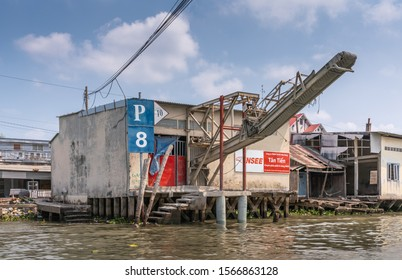 Cai Be, Mekong Delta, Vietnam - March 13, 2019: Along Kinh 28 canal. Gray suspended transportation belt over river to load barges with INSEE cement products over brown water and under blue cloudscape.