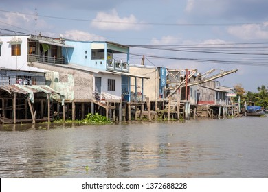 Cai Be, Vietnam - March 8, 2019 -  Traditional houses and boats on waterfront of Cai Be in Mekong River Delta of Vietnam.
