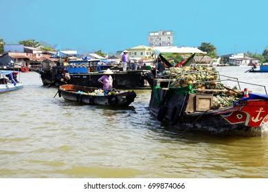 CAI RANG, VIETNAM - FEB 7, 2015 - Selling fresh pineapples from small boat  at the Cai Rang floating market,  Vietnam