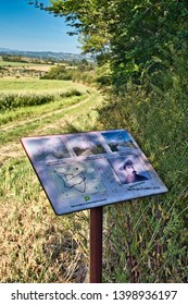 Cailhau Aude France. 05/15/19 Plaque commemorating Achille Lauge.  Images of the artists landscapes in the settings where they were painted. Farm track between the crops of rape seed leading to a wood