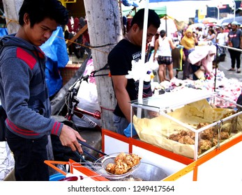 CAINTA, RIZAL, PHILIPPINES - DECEMBER 1, 2018: A vendor sells street food during the town fiesta celebration when the city government closed an entire street and turned it into a big bazaar area.
