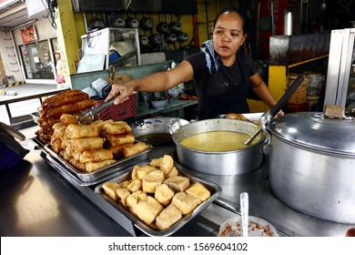 Cainta, Rizal, Philippines – November 23, 2019: Worker at a neighborhood eatery or carinderia serves cooked food to a customer.