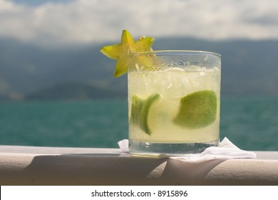 Caipirinha (cocktail) with star fruit garnish, with beautiful blue-green water and hills in the background.