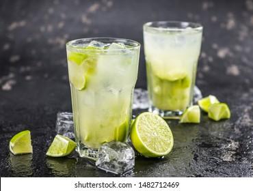 Caipirinha made with fresh limes, ice and sugar as close-up shot
