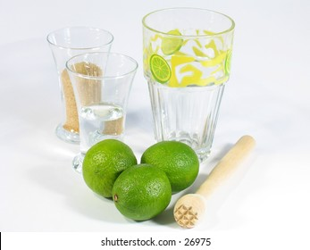 A caipirinha set with limes, a pestle, one glass with white rum and one with brown suggar and a special Caipirinha glass.