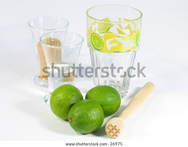 A caipirinha set with limes, a pestle, one glass with white rum and one with brown suggar and a special Caipirinha glass.