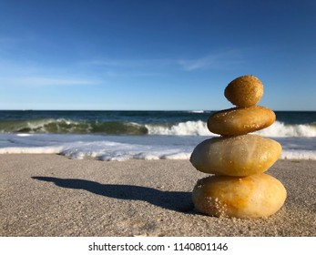 Cairn: a Beautiful Rocks Pyramid on the Beach against Ocean Waves, Foam and Blue Sky Background