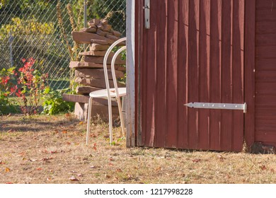 Cairn behind next to a garden shed and garden chair