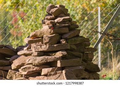 Cairn in the garden in front of wire mesh fence