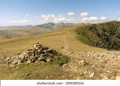 Cairn next to a stoney footpath in the Lake District, UK. The path, marked with multiple cairns, leads into the distance with the Crinkle Crags in the background below a light cloudy sky.