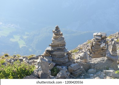 Cairn on top of mount, Switzerland. Kid is playing.