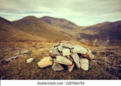 A cairn, pile of stones marking a mountain top, waypoint in the English Lake District. Summit of Outerside with Sail and Crag Hill in the distance.
