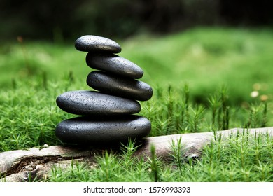 Cairn, stack of basalt rocks, in a forest surrounded by moss