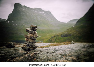 A cairn of stones on a background of mountains, an amazing landscape in the mountains of Norway, a trip to Scandinavia, a landscape of northern nature
