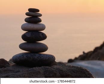 cairn at sunset, stones balances, pyramid of stones at sunset, concept of life balance, harmony and meditation
