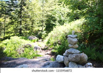Cairn with a trail in the background, in the forests of the Pyrenees, France
