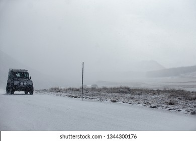 Cairngorms, Scotland - March 13 2019: Landrover defender driving in the snow on a snowy road in Scotland