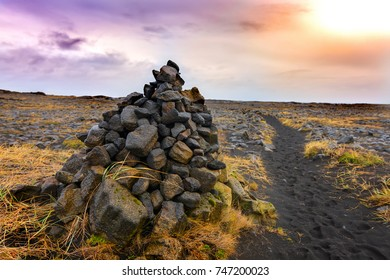 Cairns, piles of volcanic stones in Iceland, near a volcanic sand pathway