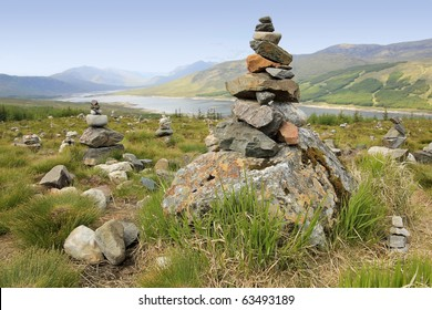 cairns or rock piles on the top of mountain overlooking loch in the highlands of scotland