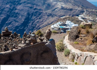 Cairns of rocks at the walking path number 9 between the cities of Fira and Oia at Santorini Island