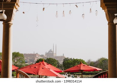 Cairo - April, 28 2019: Shot of red umbrellas in Azhar park and Cairo citadel in the background. Citadel of Saladin is one of the greatest monuments in Egypt.