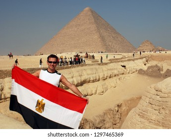 CAIRO EGYPT 11 22 10:  Man waving egyptian flag in front Great Pyramid of Giza or the Pyramid of Khufu or the Pyramid of Cheops is the oldest and largest of the 3 pyramids in the Giza pyramid