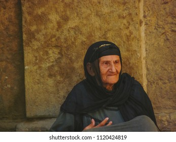 Cairo, Egypt - 2008 - An old Image for old Egyptian woman wearing traditional Egyptian Hijab resting on the walls of Al Muizz Street in Cairo, Egypt.